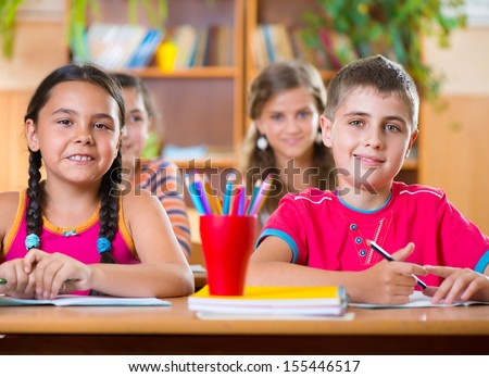 Cute schoolchildren during lesson in classroom at school - stock photo