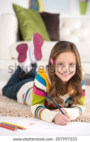 cute schoolgirl doing homework on floor. nice brunette kid drawing and smiling - stock photo