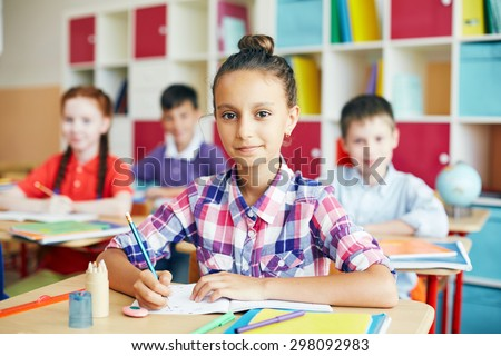 Cute schoolgirl sitting at drawing lesson - stock photo