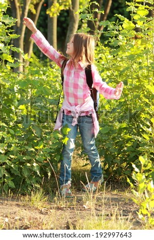 Cute schoolgirl with a school backpack goes camping in the woods - stock photo