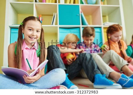 Cute schoolgirl with exercise-book looking at camera with classmates on background - stock photo