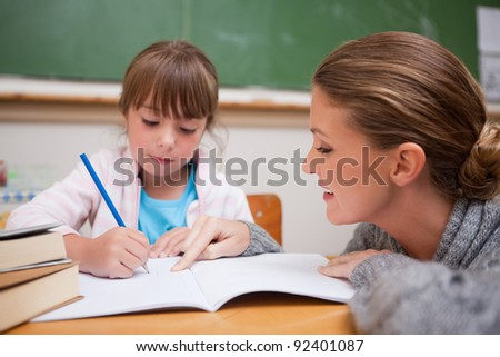 Cute schoolgirl writing a while her teacher is talking in a classroom - stock photo