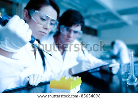 Cute scientist dropping liquid in test tubes while her partner is taking notes in a laboratory - stock photo