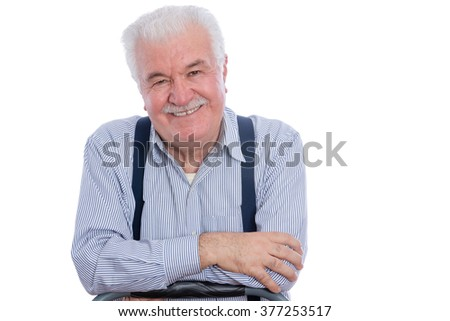 Cute senior man with mustache in white striped shirt and blue suspenders with joyful expression and folded arms over white background - stock photo