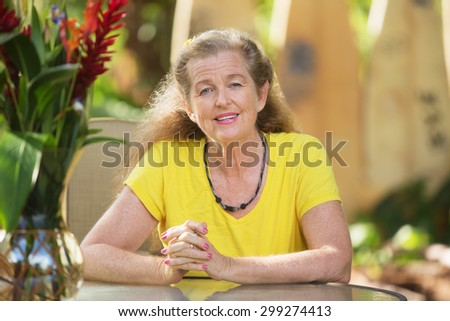 Cute senior woman sitting at table with smile - stock photo