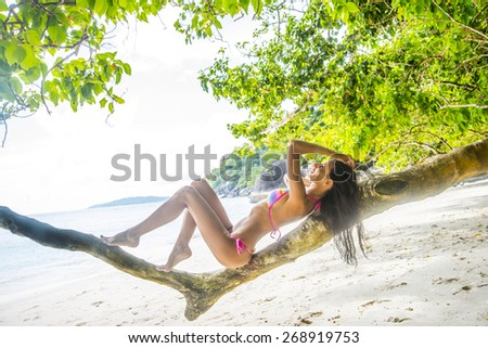 Cute sexy woman against beach island ocean or sea Female wearing colorful pink swimsuit against boat standing on coast Full length body young adult erotic girl lie on tropical tree old trunk texture  - stock photo