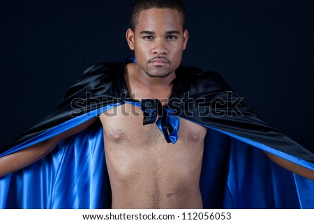 Cute shirtless black man wearing a black cape with blue satin inside, making dramatic statements with his arms and the shiny material - stock photo