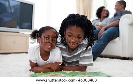Cute siblings reading lying on the floor in the living room - stock photo