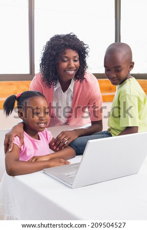 Cute siblings using laptop together with mother at home in the kitchen - stock photo