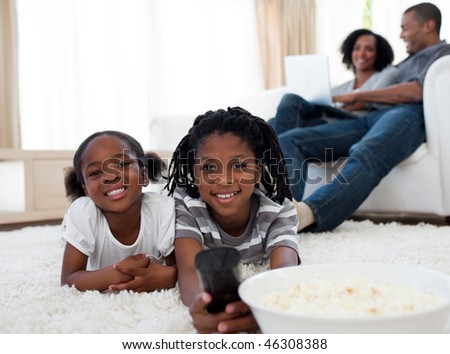 Cute siblings watching television and eating pop corn lying on the floor - stock photo