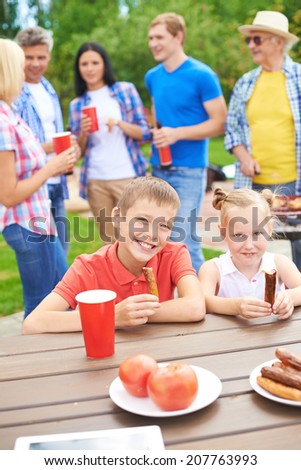 Cute siblings with sausages looking at camera at weekend with their parents and grandfather on background - stock photo