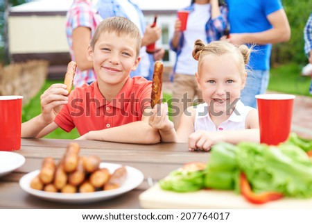 Cute siblings with sausages looking at camera at weekend with their parents on background - stock photo