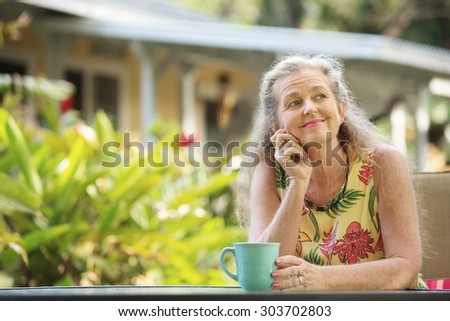 Cute single mature woman with hand on chin - stock photo