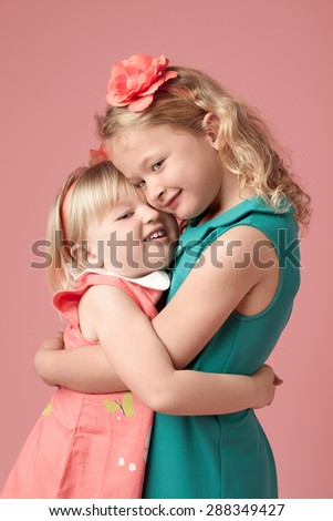 Cute Sisters hugging - stock photo