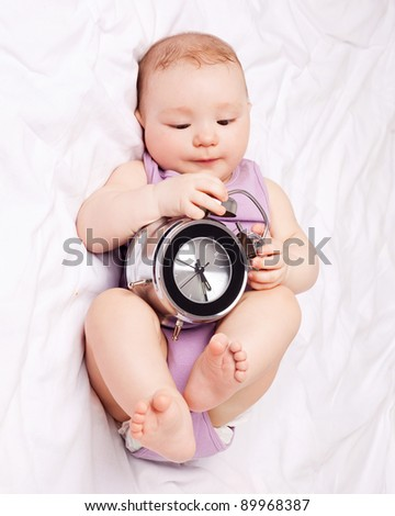 cute six months old baby in  bed at home with an alarm clock - stock photo