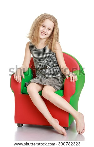 Cute skinny little girl of school age with flowing blond hair sitting on a chair. Girl sitting with no shoes softly looking at the camera-Isolated on white background - stock photo