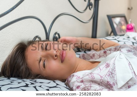 cute sleepy young girl unwilling to get up from bed - stock photo