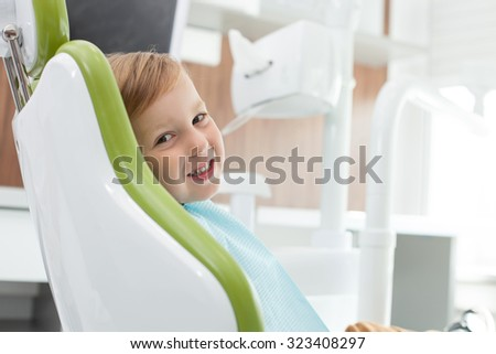 Cute small boy is visiting dentals doctor. He wants to treat his teeth. The kid is sitting in medical chair with joy. He is looking at camera and smiling - stock photo