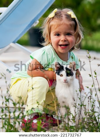 cute small girl is hug a cat, happy portrait with children and animal  - stock photo