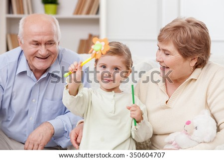Cute small girl is sitting on the sofa with her grandparents. She is holding pen and pencil with joy. The old man and woman are smiling - stock photo