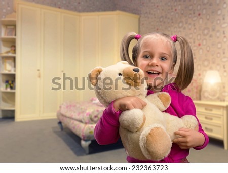 Cute small girl  with toy beart - stock photo