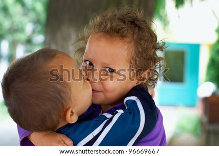 cute small gypsy girl and boy kiss. outdoors - stock photo
