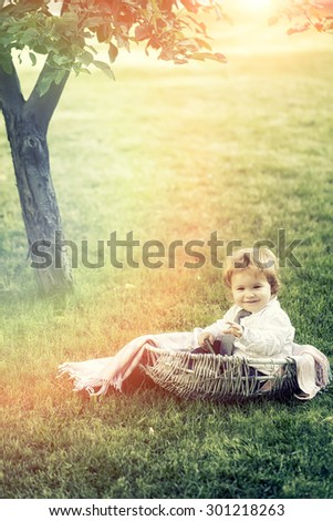 Cute small smiling happy boy with blond curly hair in formal clothes sitting on green grass and tree in basket cradle with plaid outdoor sunny day on natural background copyscape, vertical picture - stock photo