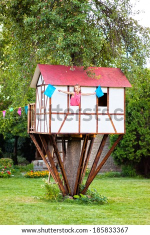 Cute small tree house for kids on backyard. Girl inside. - stock photo