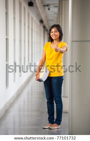Cute smiling Asian student in yellow t-shirt, blue jeans holding books at side and giving thumbs up on a modern college campus gray hallway while looking at. 20s female Thai model of Chinese descent - stock photo
