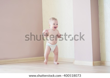Cute smiling baby boy learning to walk and make his first steps - stock photo
