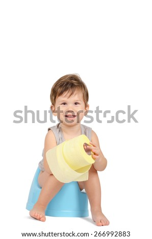 Cute smiling baby boy with toilet paper sitting on a blue potty isolated on white background - stock photo