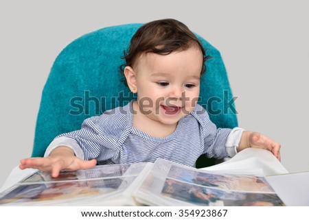 Cute smiling baby girl looking at the photo album. Selective focus on the baby head. - stock photo