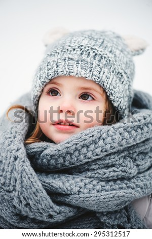 cute smiling baby girl winter close up portrait in warm knitted hat and scarf - stock photo