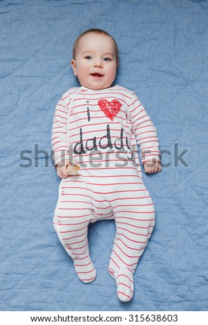 Cute smiling baby in white and red striped sleep suit lying on his back on the blue blanket. I love daddy concept. Top view. Baby looking straight at the camera. Selective focus on baby head. - stock photo