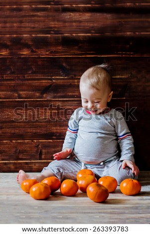 Cute smiling baby with heaps of mandarins - stock photo