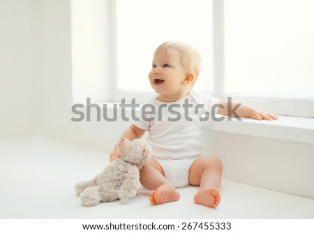 Cute smiling baby with teddy bear toy sitting at home in white room near window - stock photo