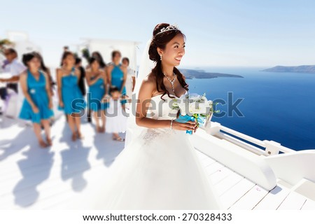 Cute smiling beautiful asian bride throws a wedding bouquet to bridesmaids in island Santorini background blue sky - stock photo
