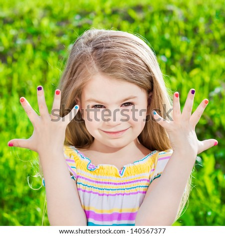 Cute smiling blond little girl with many-coloured manicure - stock photo