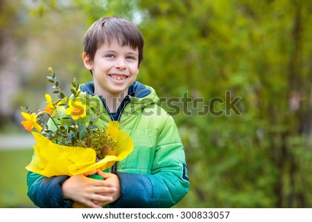 Cute smiling boy holding bouquet of daffodils outdoors - stock photo