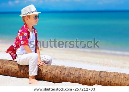cute smiling boy sitting on palm wood at sandy beach - stock photo