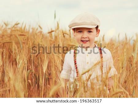 cute smiling boy walking the wheat field - stock photo