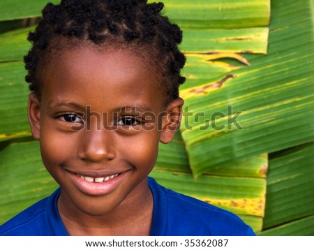 cute smiling boy with giant banana leaves in the caribbean - stock photo