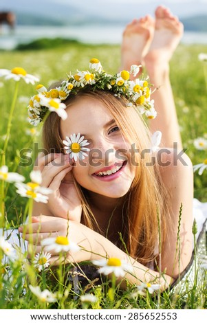 Cute smiling child girl is lying at green field with camomiles - stock photo
