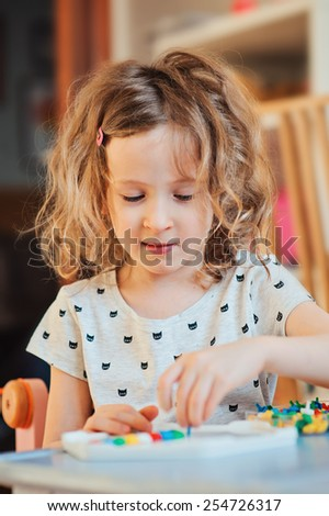 cute smiling child girl playing at home with colorful mosaic - stock photo