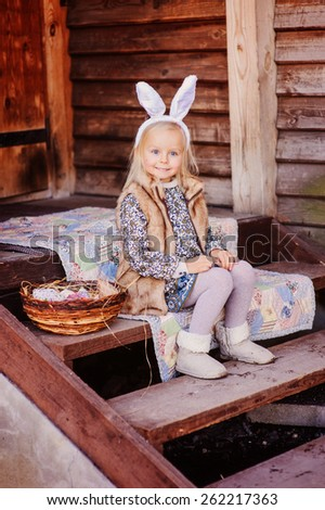 cute smiling child girl wearing bunny ears for easter sitting at country house - stock photo