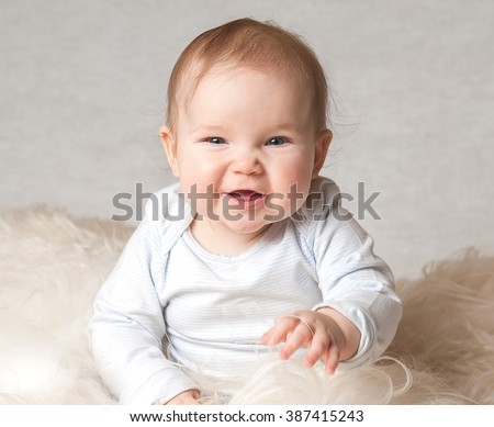 Cute smiling child on a white bed. First teeth. health 6 months baby girl sitting. textile for infant nursery - stock photo
