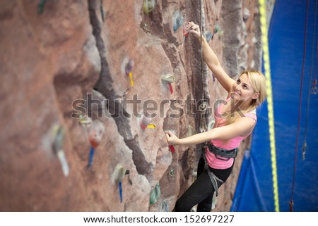 Cute smiling girl engaged in climbing - stock photo