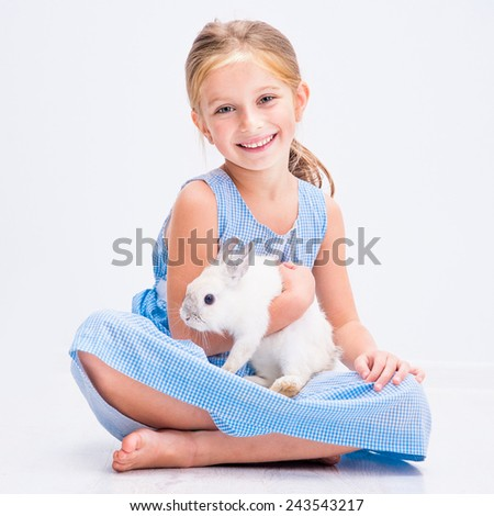 cute smiling girl in a blue dress with a white rabbit - stock photo