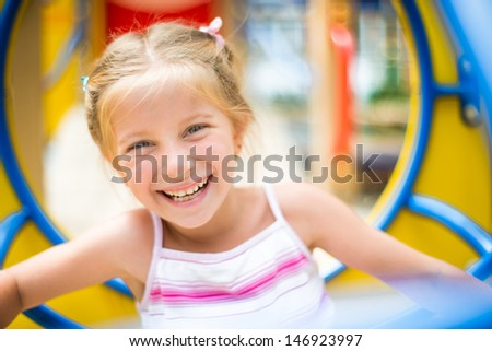 cute smiling girl on a playground - stock photo