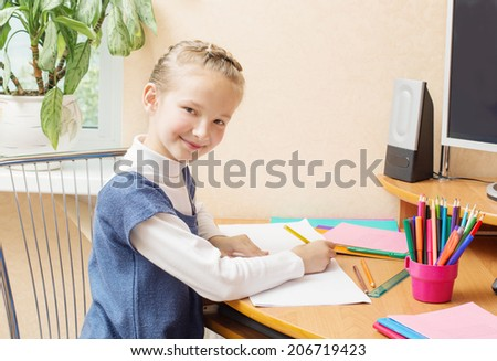 Cute smiling girl sitting at desk - stock photo
